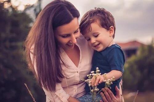 Una mamma con in braccia suo figlio, mentre guardano insieme un fiore