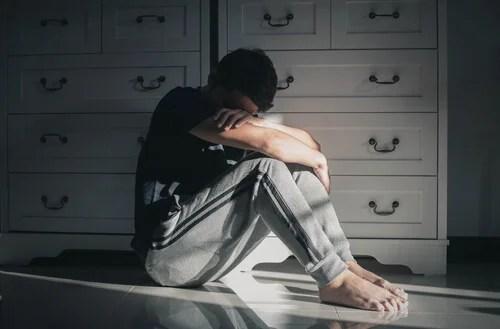 Hombre en el suelo pensando en el suicidio