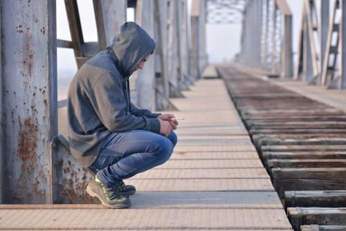 Adolescente triste en cuclillas que no ha superado el periodo del duelo