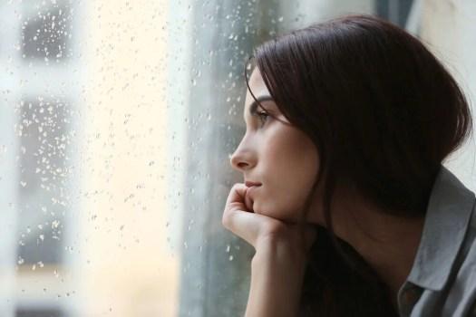 Mujer mirando por la ventana soñando con ser feliz