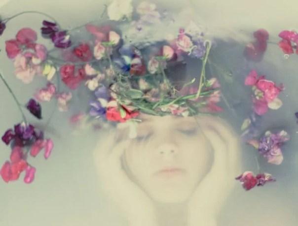 mujer bajo el agua con una corona de flores