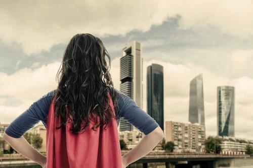 Mujer con capa roja de superheroína pensando en héroes
