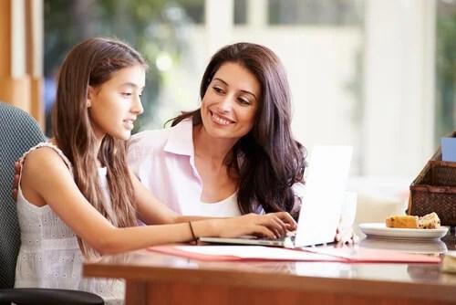 Madre con su hija mientras ella está con el ordenador