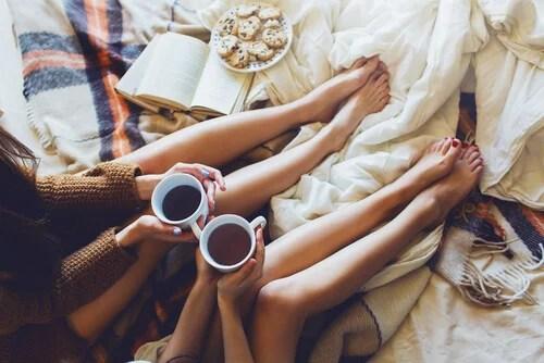 Amigas sentadas en la cama tomando café