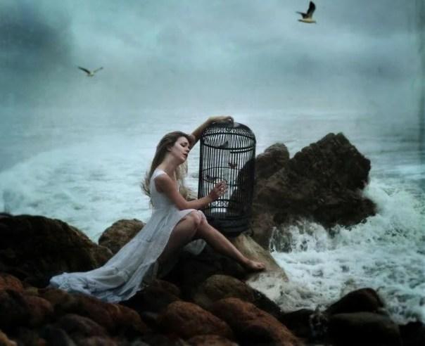Mujer sufriendo sentada al lado del mar