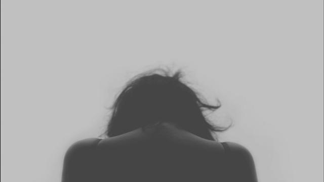 Mujer de espaldas con la cabeza hacia abajo con dolor crónico