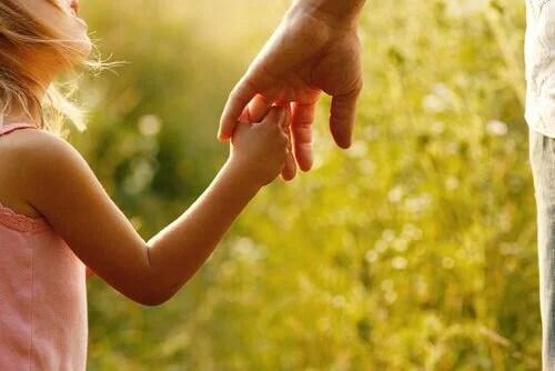 Niña agarrando la mano de su madre