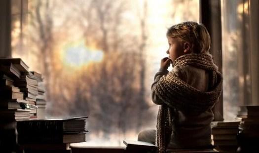 Niño con bufanda mirando por la ventana