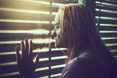 Mujer mirando por la ventana como símbolo de la pregunta qué hacer con tu vida