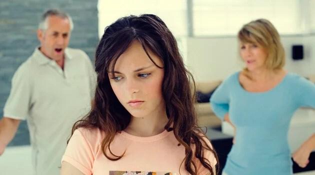 adolescente enfadada con sus padres simbolizando la teoría de la reactancia psicológica