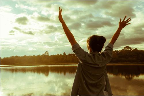 Mujer con las manos hacia arriba pensando en la excelencia
