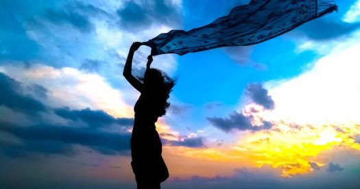 mujer con velo al viento simbolizando la abundancia