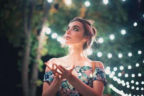 Mujer paseando por un lugar natural con luces pensando en el efecto de la consciencia y conciencia
