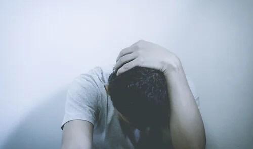 Hombre preocupado mirando hacia abajo que sufre comorbilidad de la depresión