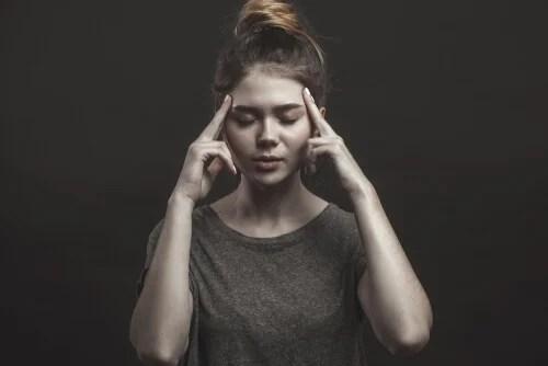 Mujer pensando con los ojos cerrados y las manos en la frente en la heurística de la afectividad