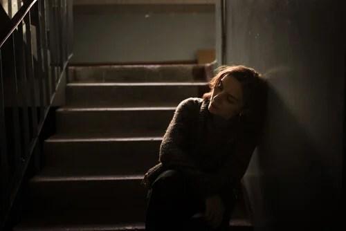 Mujer apoyada en unas escaleras