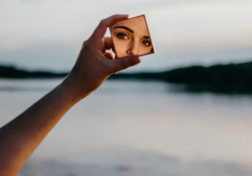 Mujer mirándose al espejo debido a la autoestima excesiva