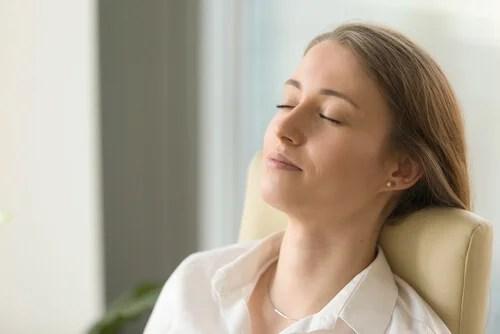 Mujer con los ojos cerrados intentando resolver los problemas para conciliar el sueño