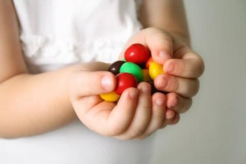 Niña con caramelos en las manos