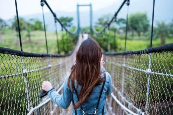 Chica caminando por un puente colgante
