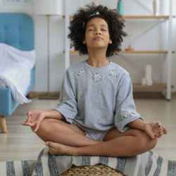 black girl meditating in room with eyes closed