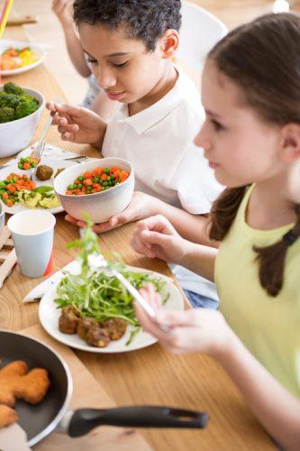 High angle of children eating vegetables for dinner at school