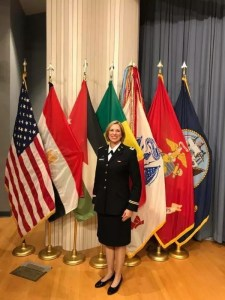 Lady in Military Unifrom in front of the US Flag and Armed Forces flags