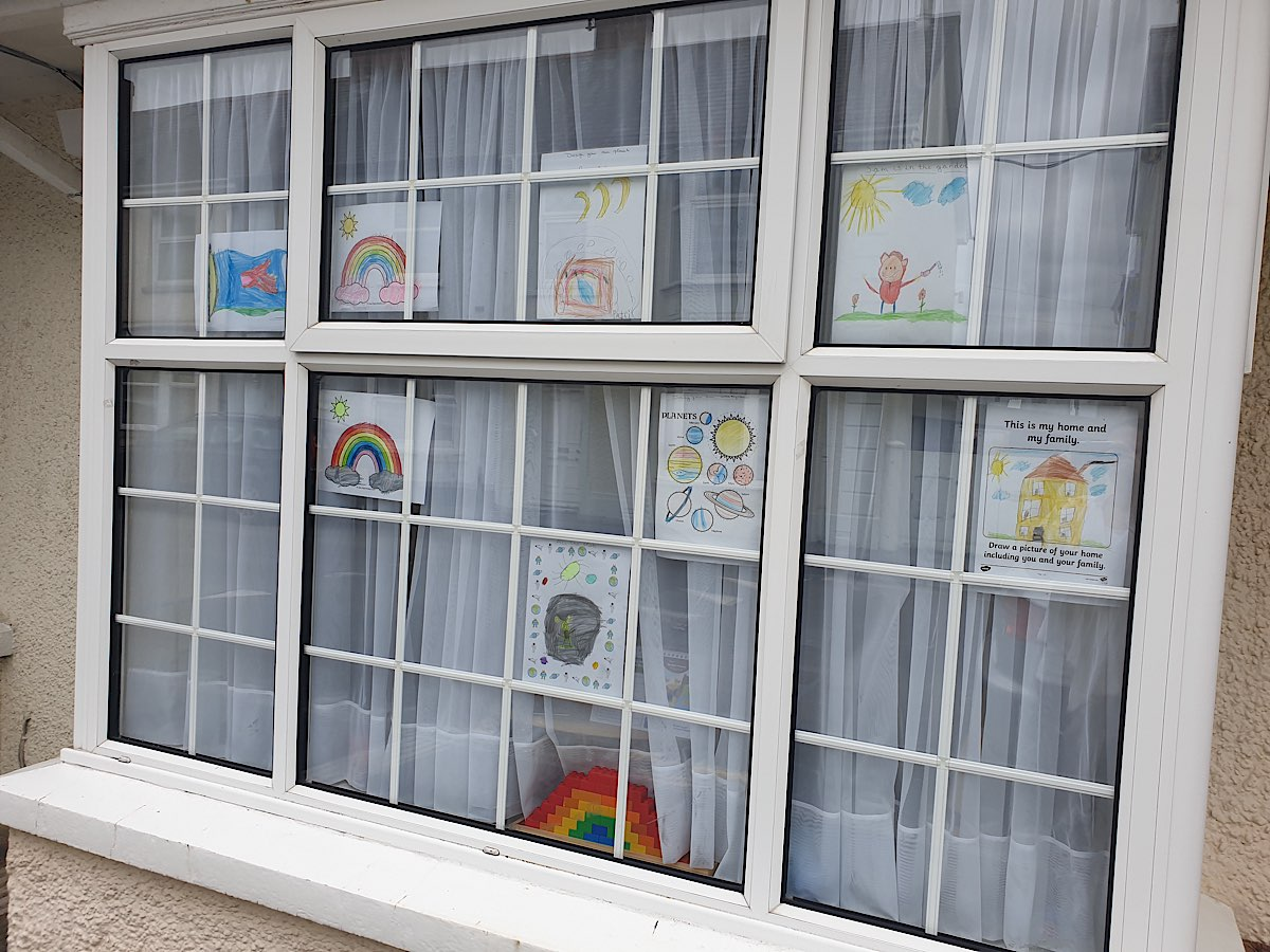 A window with many small panes showing colourful drawing by children