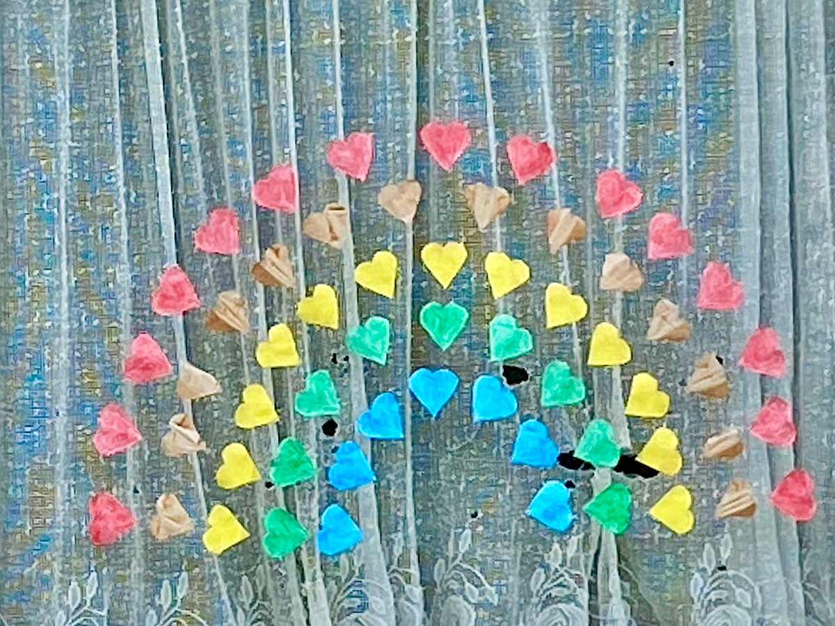 A window with a rainbow made out of coloured heart shapes