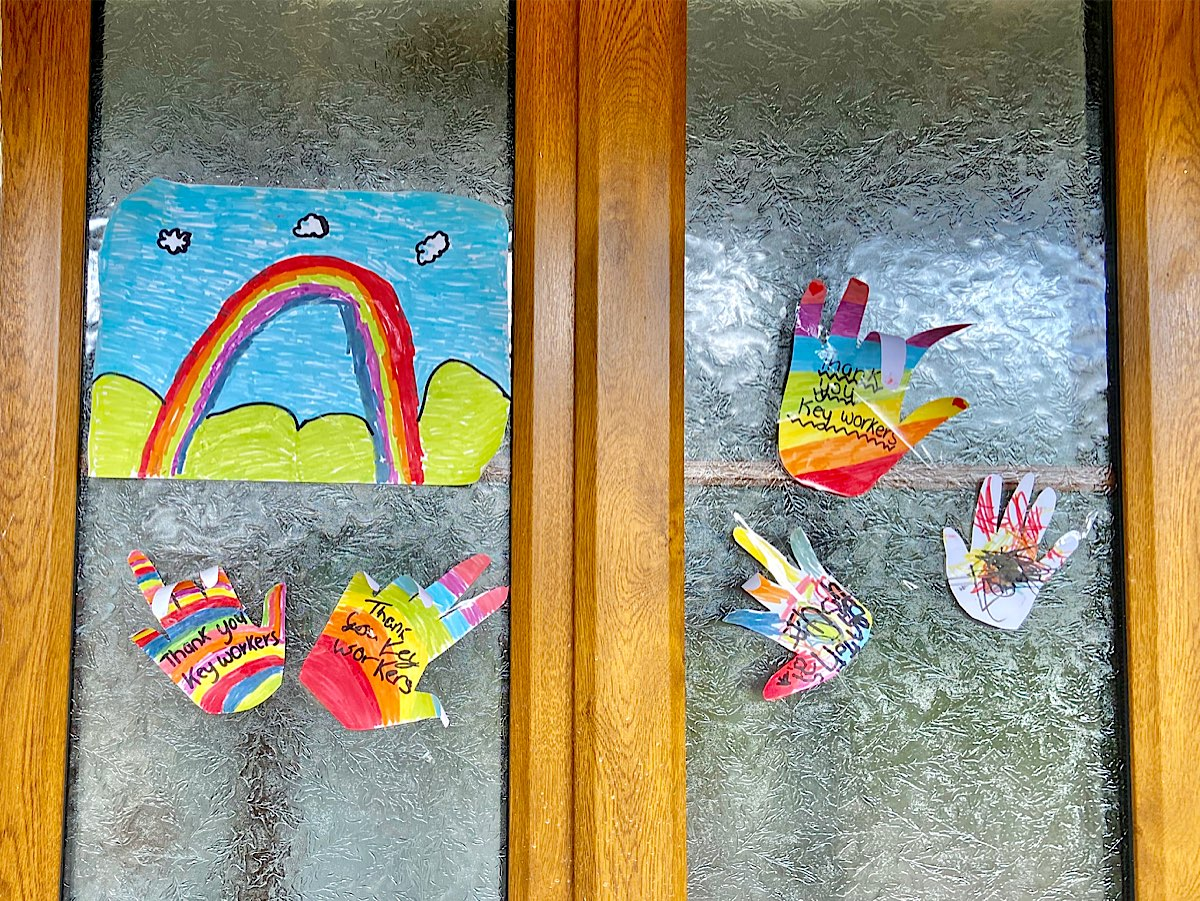 A window with a rainbow painting and several multi-coloured hand shapes