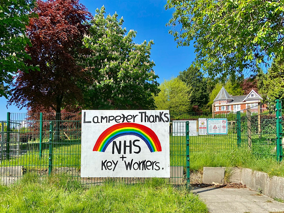 This is a great banner image with the words Lampeter Thanks above the rainbow, then NHS + Key Workers below it. It is shown here in situ with the park and trees behind it.