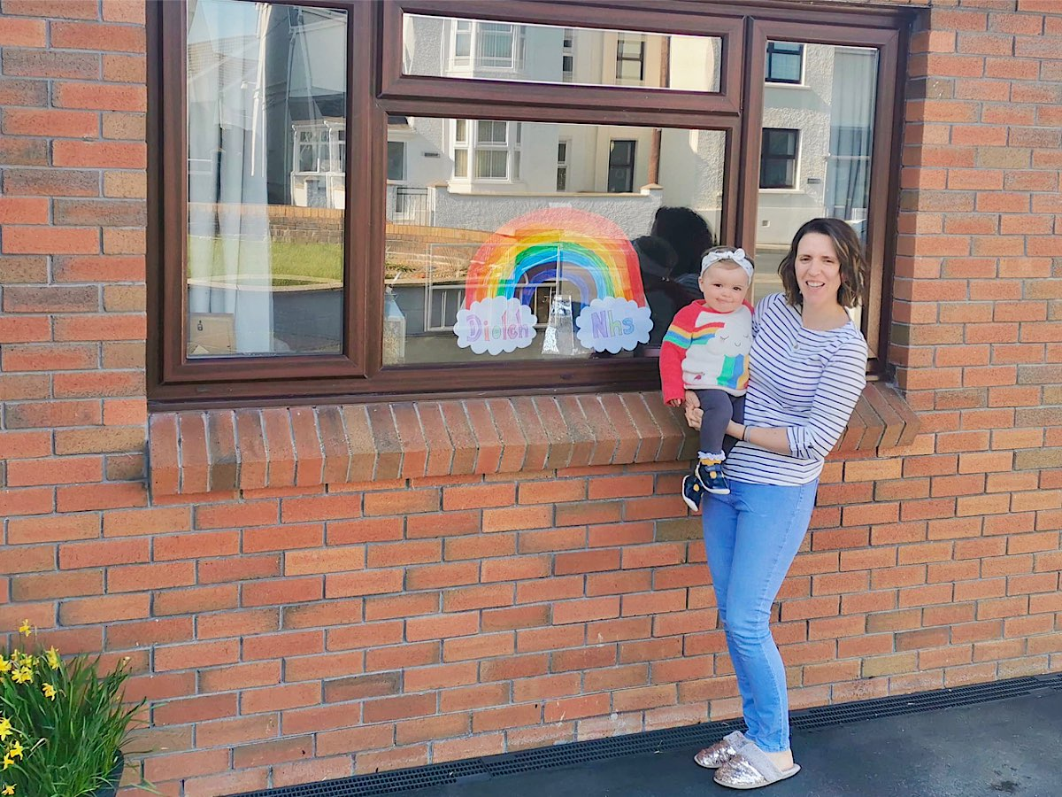 A mother holds her baby, dressed in very cute rainbow coloured clothes with a sleeping cloud shape on the front up to the window where a rainbow is sprouting out of 2 loud shapers, one says Diolch and the other says NHS - Diolch NHS