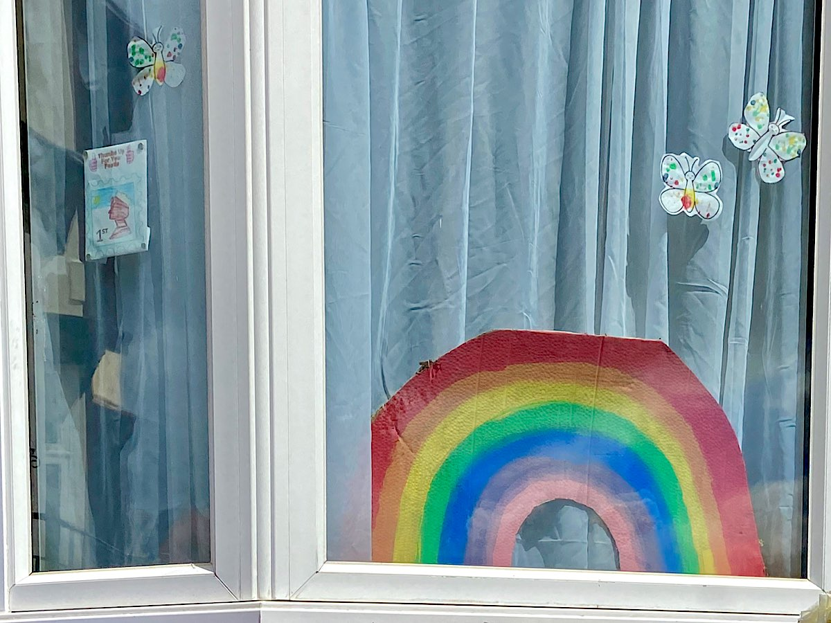 A cut out rainbow in a window surrounded by colourful butterflies