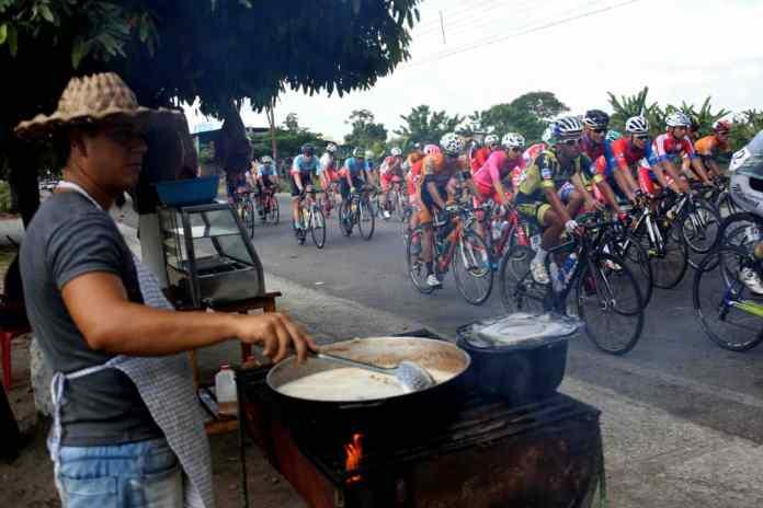 Foto/Carlos Eduardo Ramírez- Un parroquiano, a la vera del camino, prepara un suculento hervido, con fondo de los corredores que hacen vida en la competencia.