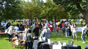 A crowd of people gather in a park at vendor tables
