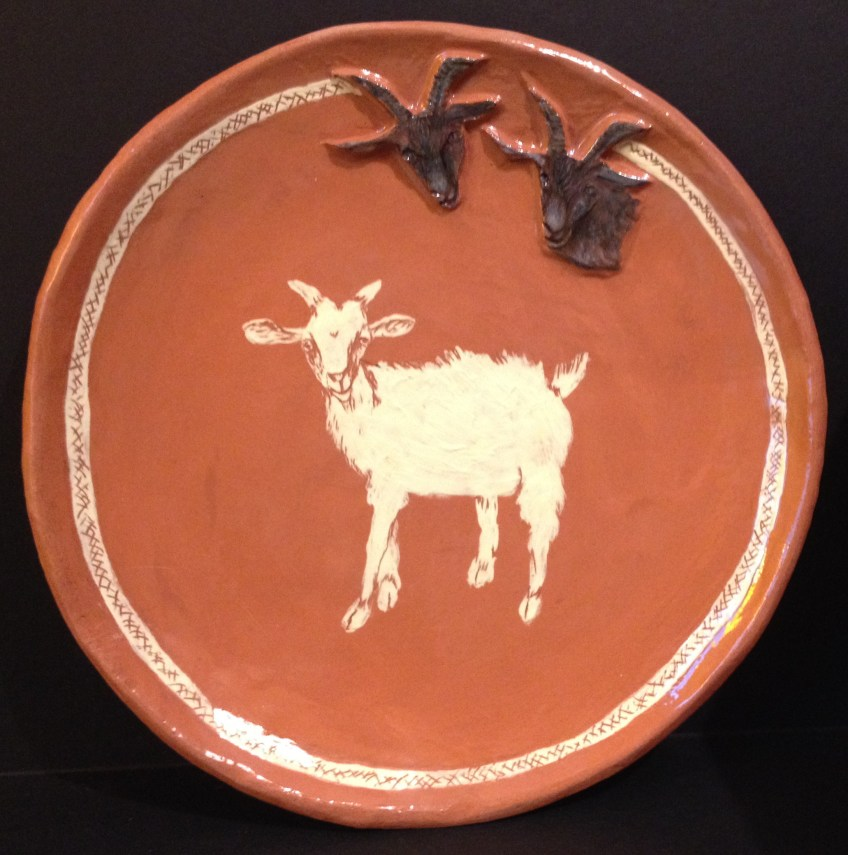 Red earthenware goat bowl, painted with yellow slip.