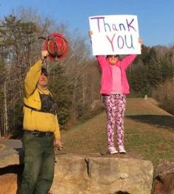 A girl proudly waves her sign proclaiming her gratitude at the efforts being made by the men and women bravely fighting the fires.