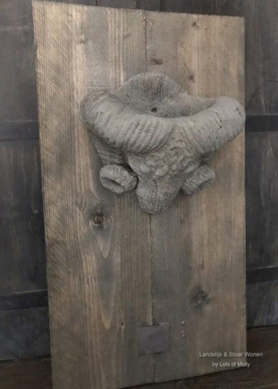 Stoer wandpaneel van hout met een betonnen ramskop, Aura Peeperkorn