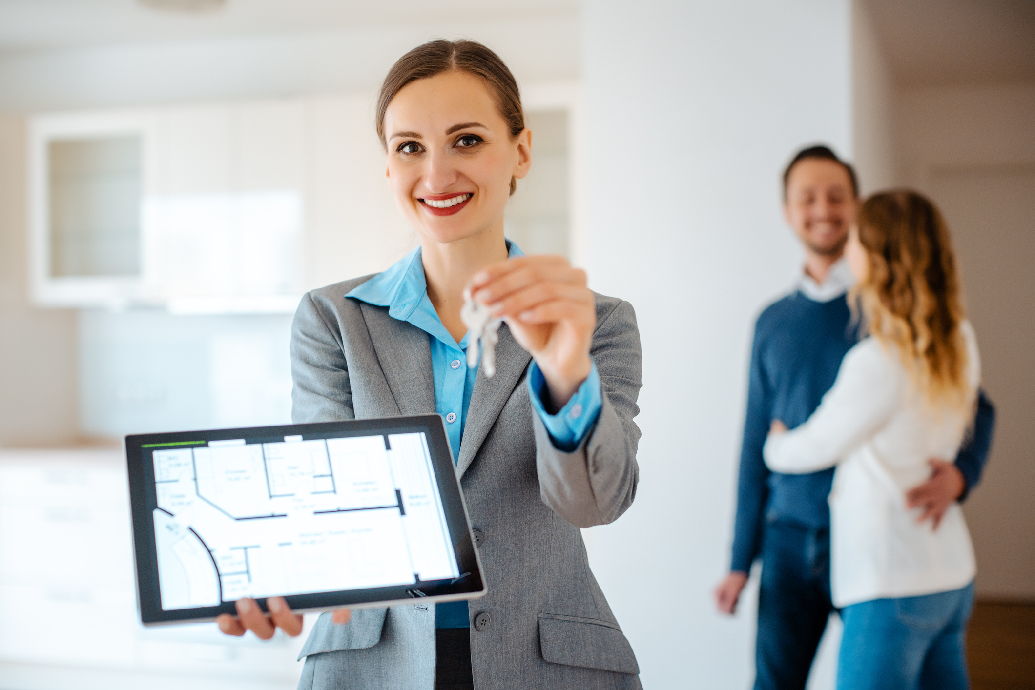 A female landlord showing the screen of her tablet and using a property management software like Buildium while showing a house.