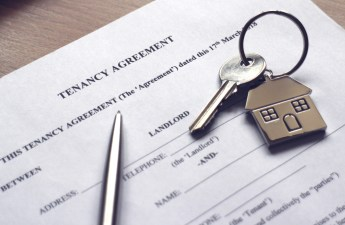 "A house key resting on paperwork titled, ""Tenant Agreement."" RentPrep tenant screening"