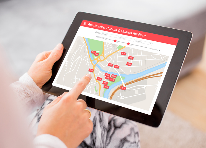 person-using-tablet-displaying-map-with-apartments-rooms-and-homes-for-rent