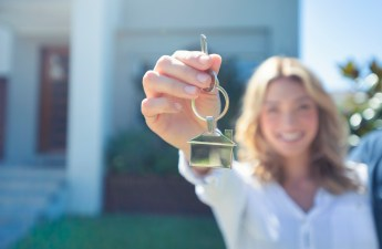 woman-smiling-and-holding-house-key-towards-camera-while-standing-in-front-of-house