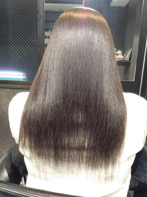 鏡の前に座っている女性です。真後ろから写真を撮りました。髪の毛の長さはロングヘアーで胸辺りまであります。黒髪でダブル天使の輪が美しいです。女性の着ている服はセーターで色は白です。美容室の鏡が一緒に写っています。座っている椅子の色は黒色です。真ん中辺りに穴が空いている状態です。