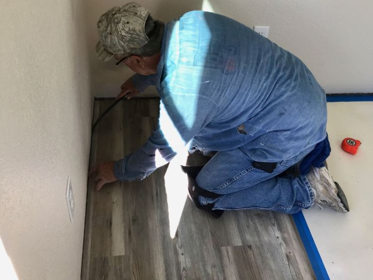 Gene sets the last piece of flooring in place