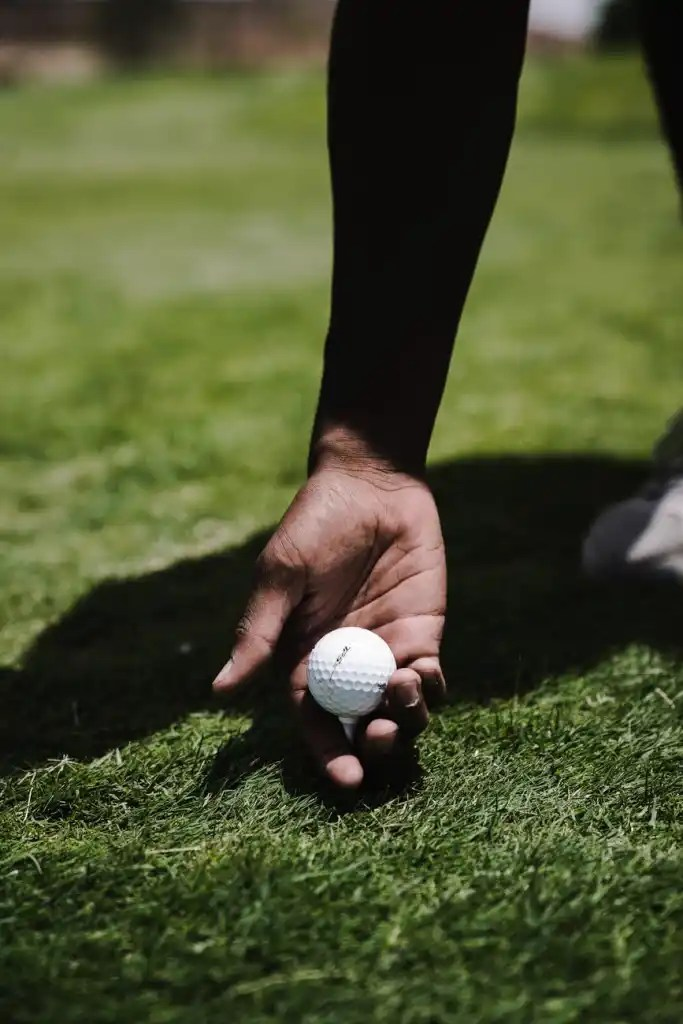 person holding white golf ball