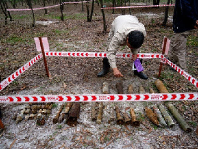Team Leader checking the condition of UXO found at the site in preparation for destruction of the dangerous ordnance in situ – or In place.