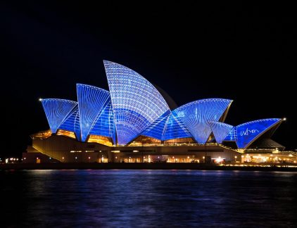 An image of the Sydney Opera House, lit up at night
