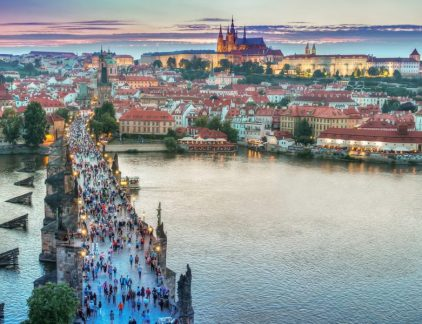 A view of the Charles Bridge and the Prague Castle at dusk