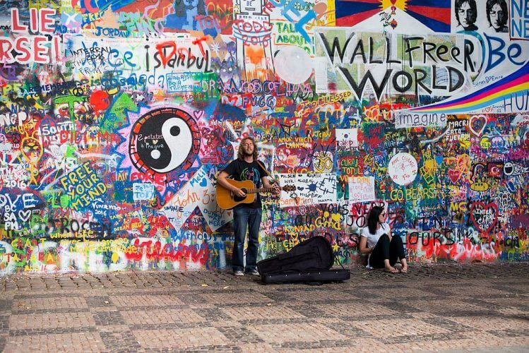 A street musician in the front of the John Lenon wall in Prague