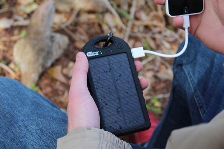 An image of a solar charger being used by a backpacker in the woods